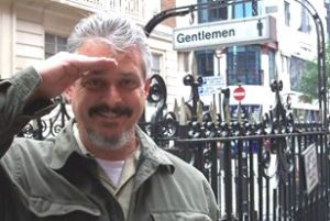 Ned salutes in front of London Gentlemen sign